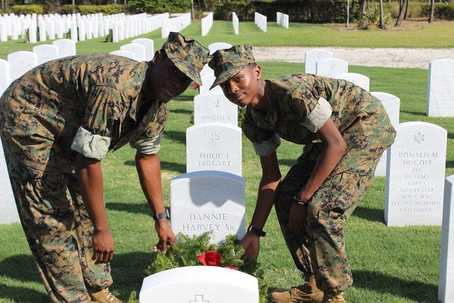 Cadet Second Class Christopher Harvey and Cadet Private Tyler Harvey place a wreath at their grandfathers grave marker.
